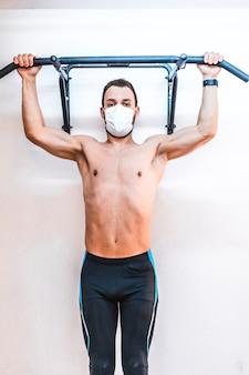 Um paciente sem camisa realizando uma dominada no ar. fisioterapia com medidas de proteção para a pandemia de coronavírus, covid-19. osteopatia, quiromassagem terapêutica