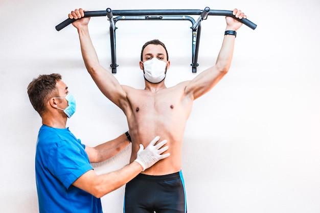 Um paciente sem camisa trabalhando com um fisioterapeuta fazendo um pull-up. fisioterapia com medidas de proteção para a pandemia de coronavírus, covid-19. osteopatia, quiromassagem terapêutica