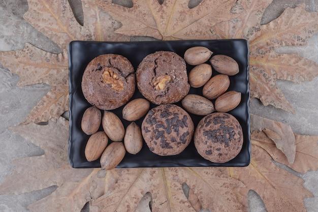 Um pacote de biscoitos e nozes em uma bandeja e um monte de folhas de plátano no mármore