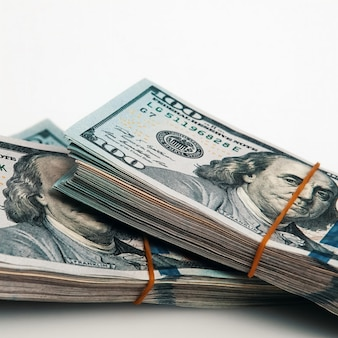 Um pacote de cem notas de dólar em um branco. isolado