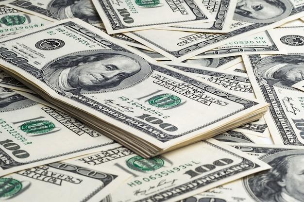 Um pacote de cem notas de dólar no fundo de dólares dispersados. vista em ângulo
