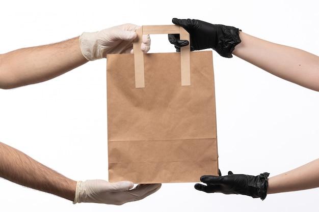 Um pacote de comida de papel de vista frontal sendo entregue de fêmea para macho em branco