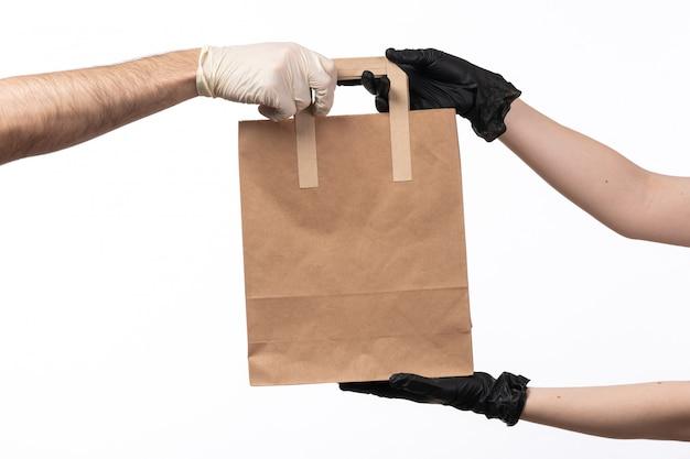 Um pacote de comida de papel vista frontal sendo entregue de fêmea para macho, tanto em luvas em branco