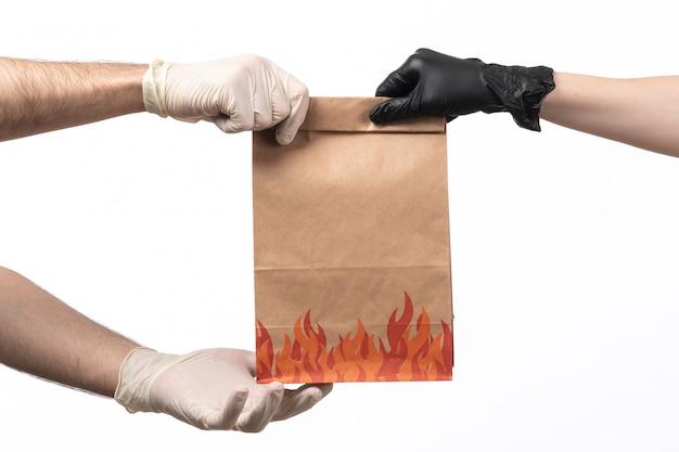 Um pacote de comida de vista frontal sendo entregue de fêmea para macho nas mãos em branco
