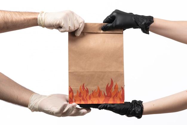 Um pacote de comida marrom vista frontal sendo entregue fromt feminino para masculino