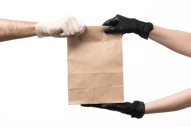 Um pacote de comida papaer vista frontal sendo entregue a partir de fêmea de macho tanto em luvas em branco