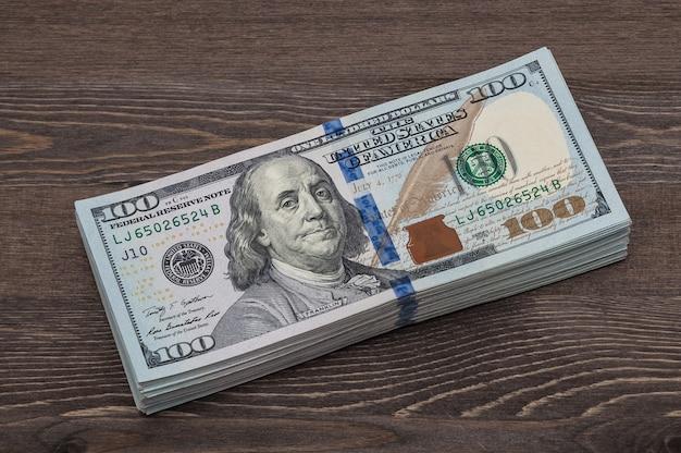 Um pacote de denominações de dez mil dólares americanos. no contexto de uma mesa de madeira.