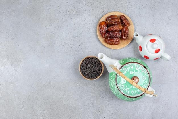 Um pacote de dois bules, uma pequena tigela de folhas de chá e um punhado de tâmaras sobre fundo de mármore.