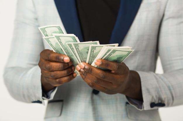 Um pacote de dólares nas mãos de um homem africano