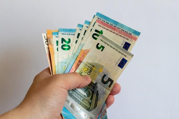 Um pacote de euros nas mãos sobre um fundo branco notas de euro em um fundo branco