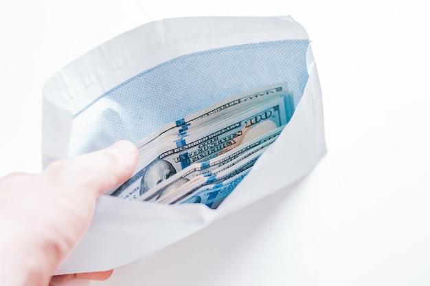 Um pacote de notas de cem dólares está em um envelope. o conceito de suborno e corrupção