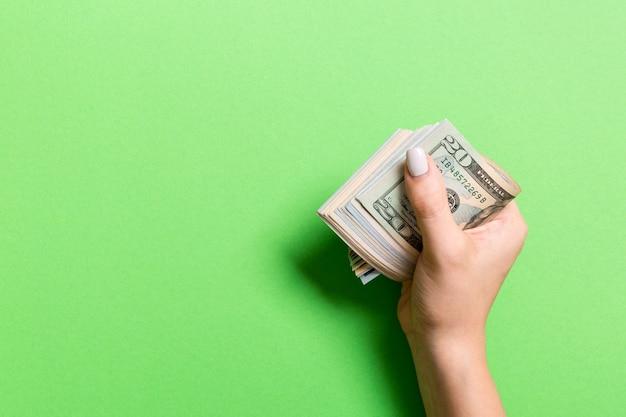 Um pacote de notas de dólar diferentes na mão feminina em fundo colorido. conceito de salário com espaço da cópia