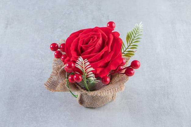 Um pacote de rosa vermelha, na mesa branca.