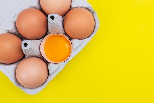 Um pacote de seis ovos marrons com uma gema aberta e laranja em fundo amarelo