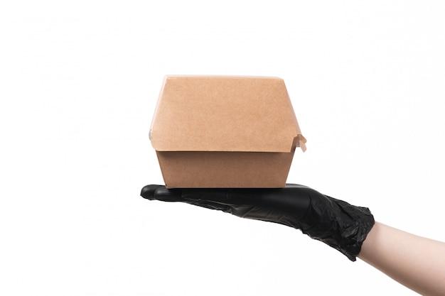 Um pacote de vista frontal comida em luvas pretas, segurando no branco