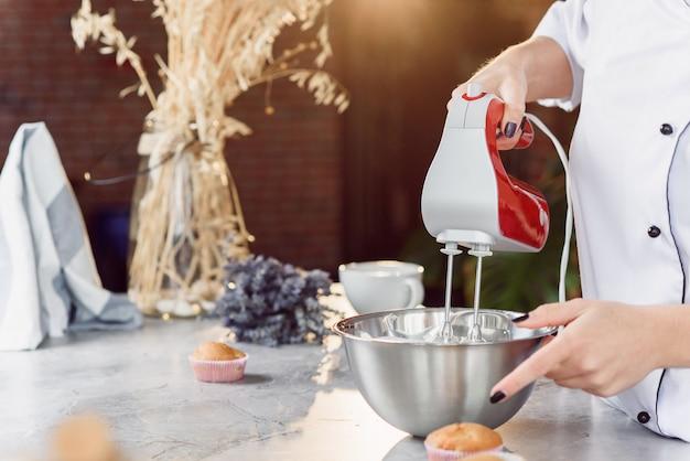 Um padeiro feminino mistura um creme de leite fresco em um prato fundo com uma batedeira vermelha. feche a foto.