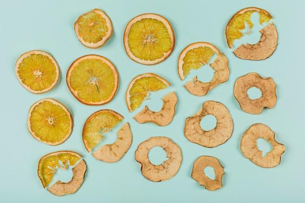 Um padrão de anéis de laranja e maçã secas em turquesa