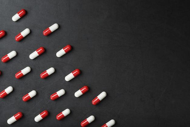 Um padrão de cápsulas de comprimidos vermelhos e brancos em um fundo preto. produtos farmacêuticos, remédios, vitaminas