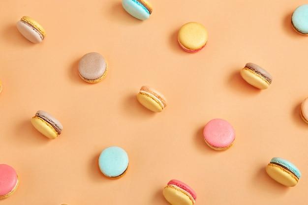 Um padrão de macarons de cookies franceses coloridos sobre fundo amarelo pêssego
