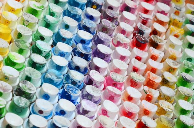 Um padrão de muitos bicos de um pulverizador de tinta para desenhar graffiti, manchado em cores diferentes.