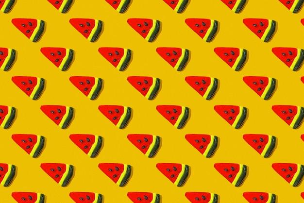 Um padrão de pirulitos de frutas coloridas em forma de fatias de melancia em um fundo amarelo. postura plana