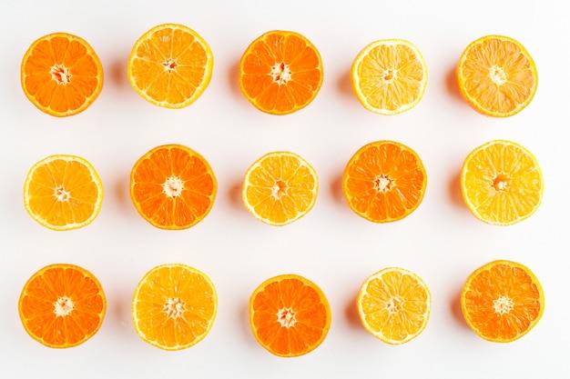 Um padrão de tangerinas laranja e amarelas cortadas ao meio em um branco