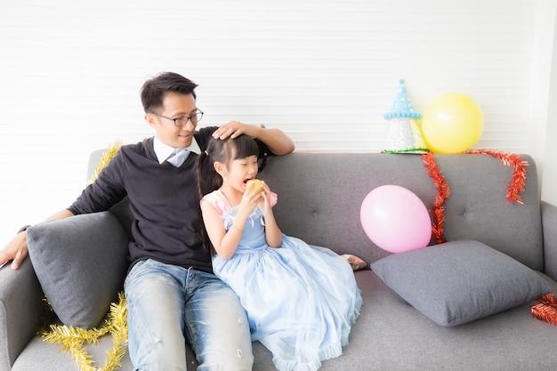 Um pai asiático com uma roupa tailandesa casual está esfregando a cabeça da filha em um vestido azul com um rosto sorridente e comendo frutas no sofá da sala de estar pela manhã.