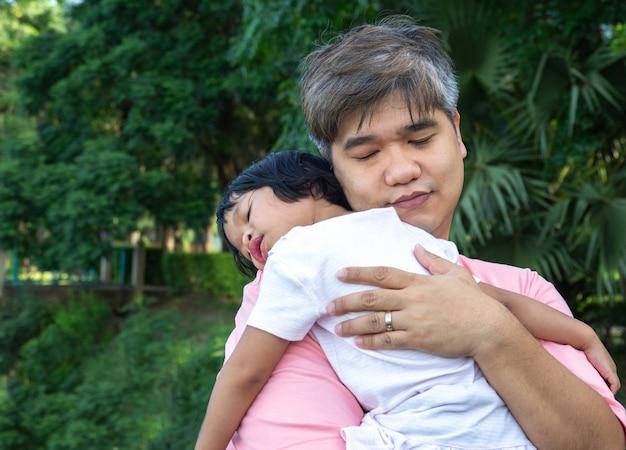 Um pai asiático está carregando uma linda filha para o peito e a filha está deitada no peito do pai.