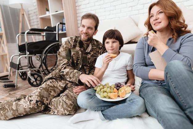 Um pai com deficiência em uniforme militar está comendo frutas.