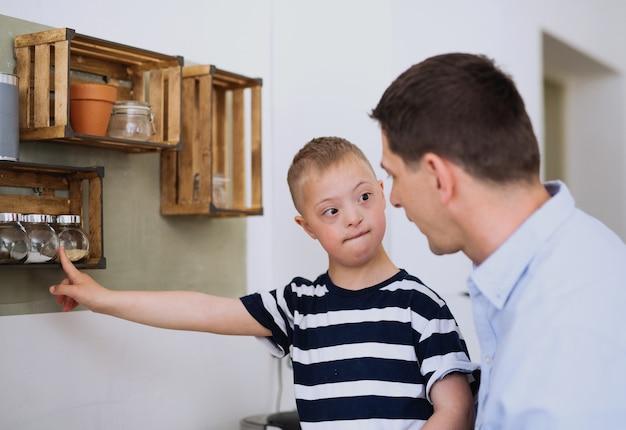 Um pai com filho de síndrome de down feliz dentro de casa na cozinha, cozinhando.
