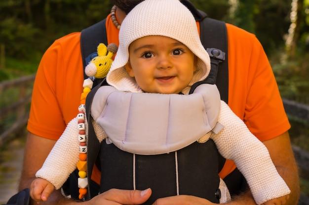 Um pai com o bebê em uma mochila indo para passerelle de holzarte na floresta ou selva de irati, ao norte de navarra na espanha e nos pirineus atlânticos da frança