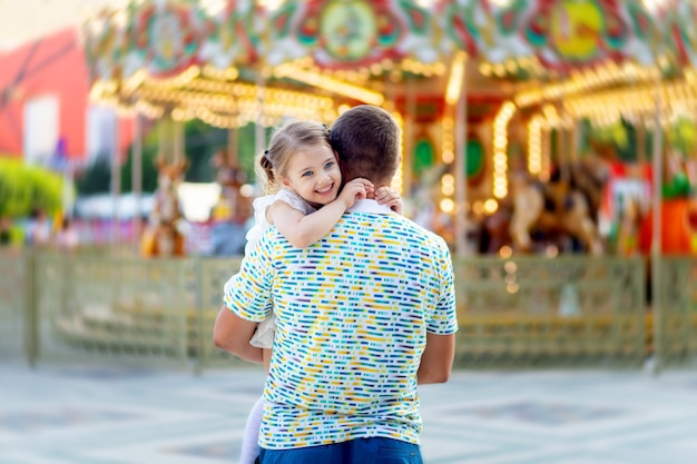 Um pai com um filho uma filha uma menina em um parque de diversões no verão de férias está se divertindo e sorrindo de felicidade