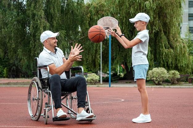 Um pai deficiente brinca com seu filho na rua. conceito de cadeira de rodas, pessoa com deficiência, vida plena, pai e filho, atividade, alegria.