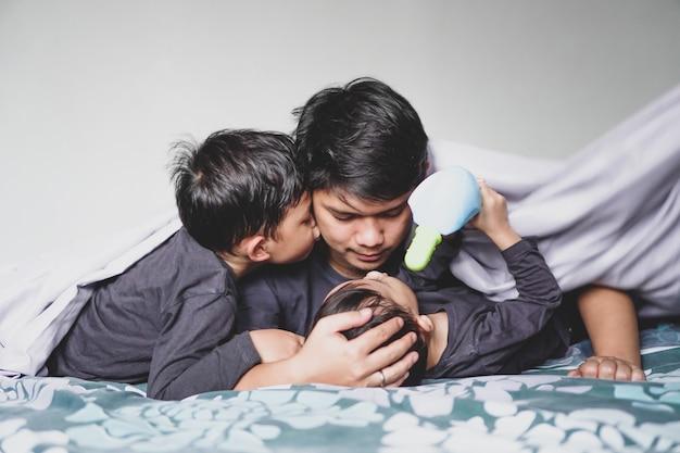 Um pai e seus dois filhos estão brincando juntos na cama