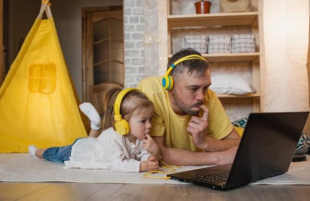 Um pai e sua filha estão deitados no chão com fones de ouvido amarelos, olhando para um laptop e segurando um dedo na boca. surpresa e deleite