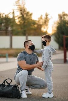 Um pai e um filho estão em um campo de esportes com máscaras após o treino durante o pôr do sol.