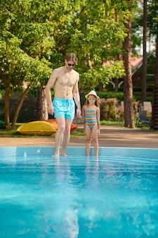 Um pai e uma filha passando um tempo na piscina