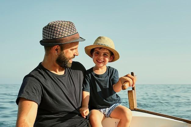 Um pai ensina a velejar para seu filho em um barco clássico