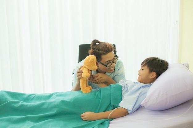 Um pai está segurando a mão dele. e encorajando o filho que está gravemente doente e descansando na cama em um hospital