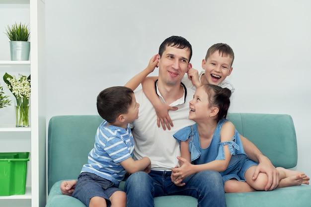 Um pai feliz com muitos filhos e seus filhos está sentado em um sofá azul