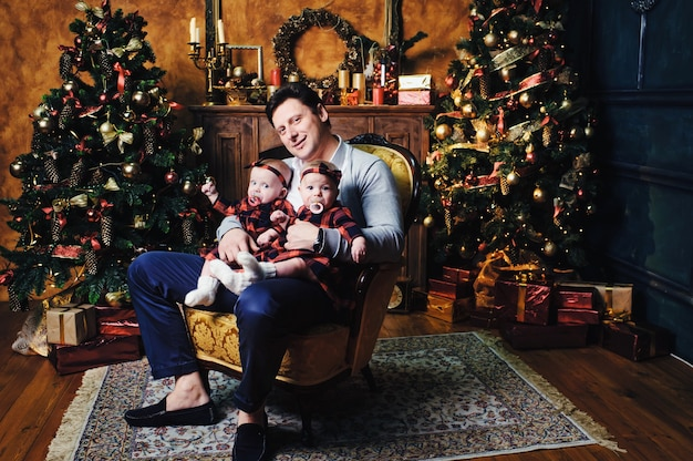 Um pai feliz com seus filhos no interior de uma casa de ano novo no fundo de uma árvore de natal