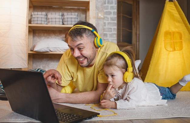 Um pai feliz com sua filha está deitado no chão em fones de ouvido amarelos, rindo enquanto olha para um laptop. jogos conjuntos de pai e filha