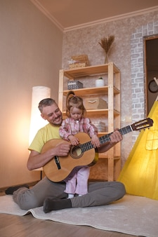 Um pai feliz com uma filha pequena aprende a tocar violão sentado em casa no chão perto da tenda amarela. pai feliz