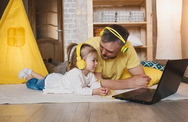 Um pai feliz e a filha dele deitam-se no chão com fones de ouvido amarelos e olham para o computador. cabana amarela
