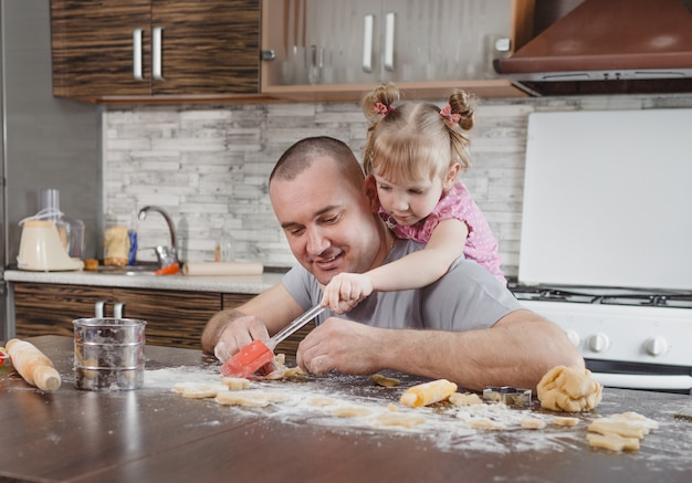 Um pai feliz e sua filha cozinham biscoitos juntos na cozinha. cozinha conjunta, valores familiares