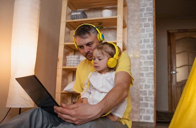 Um pai feliz e sua filha estão sentados no chão com fones de ouvido amarelos e olhando para um laptop. o conceito de felicidade familiar