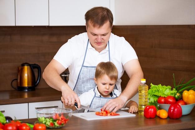 Um pai feliz e um filho pequeno preparam uma salada com legumes na cozinha.