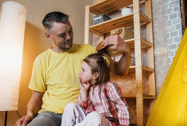 Um pai feliz em uma camiseta amarela penteia cuidadosamente o cabelo de sua filha enquanto brincam juntos no chão em casa.