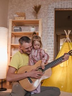 Um pai feliz toca violão para sua filha. cuidado e educação de crianças