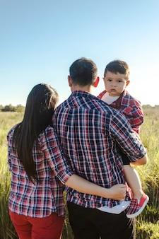 Um pai segurando seu filho nos braços, enquanto a mãe o abraça, na campina